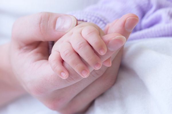 Mother holding baby's hand | PregnancyAndBaby.com