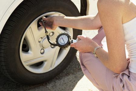 Woman checking tire pressure | Sheknows.com