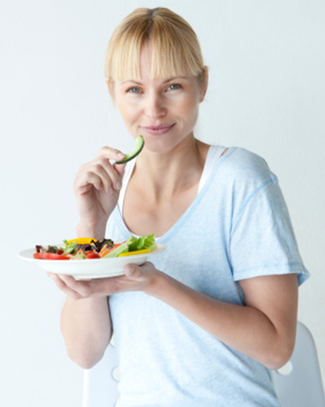 Woman eating salad | Sheknows.com