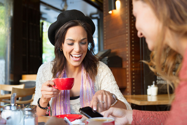 Women talking and laughing at a cafe | Sheknows.com