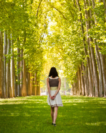 Woman walking among trees | Sheknows.com