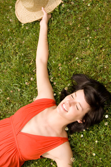 Happy woman lying in grass