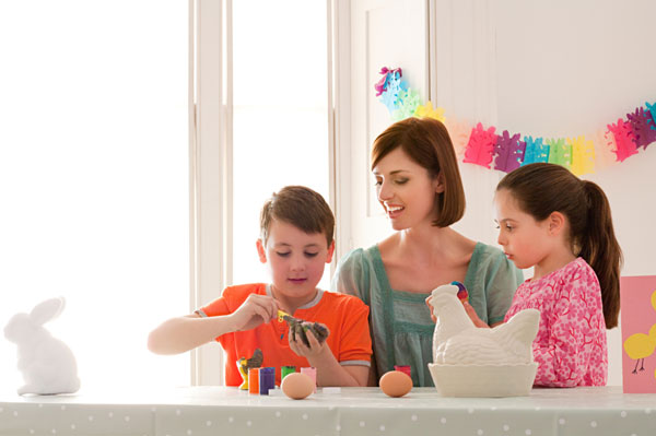 Mother and children decorating Easter eggs