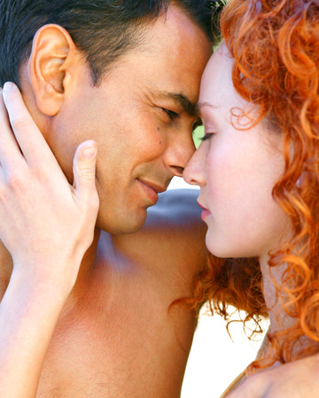Redheaded woman kissing man