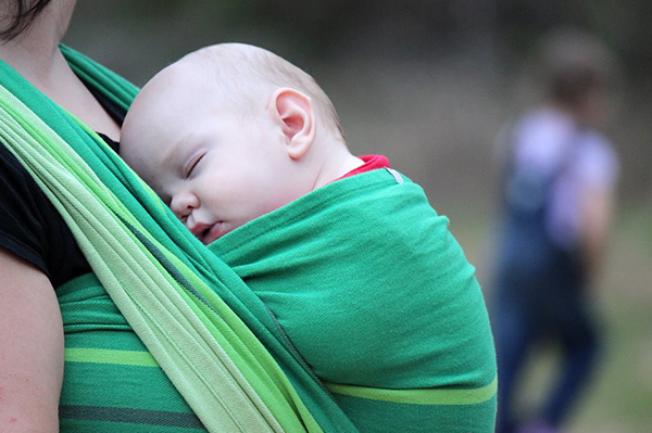 Mother holding baby in sling-Babywearing 101