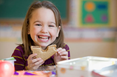 Young girl eating sandwich