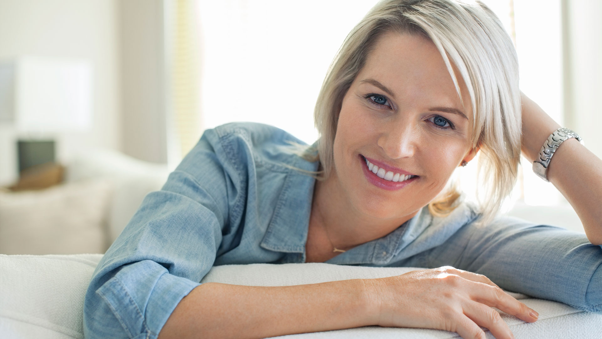 Portrait of smiling woman relaxing on sofa
