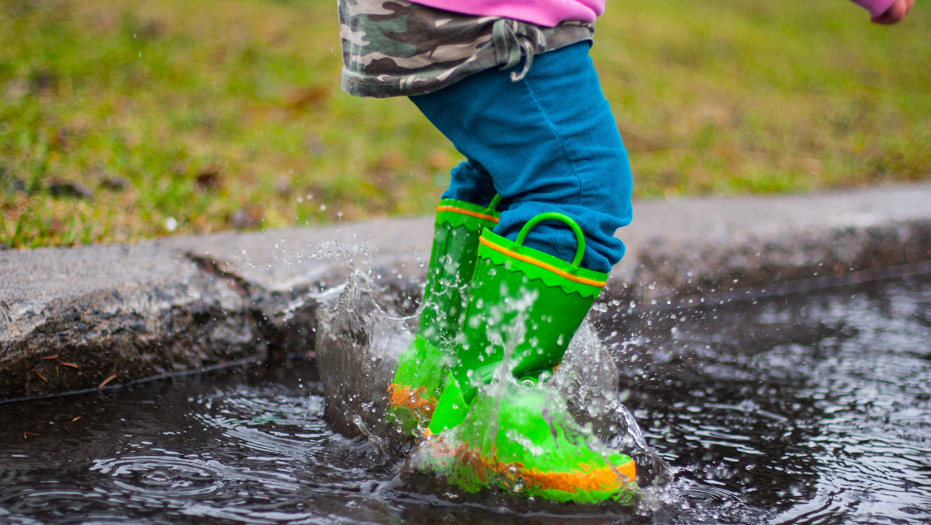 Toddler splashing in puddle