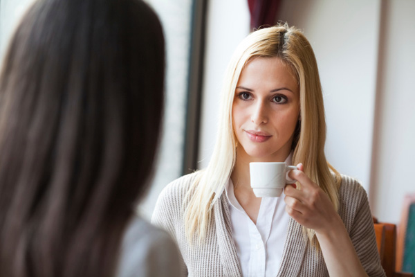 Woman talking to friend over coffee