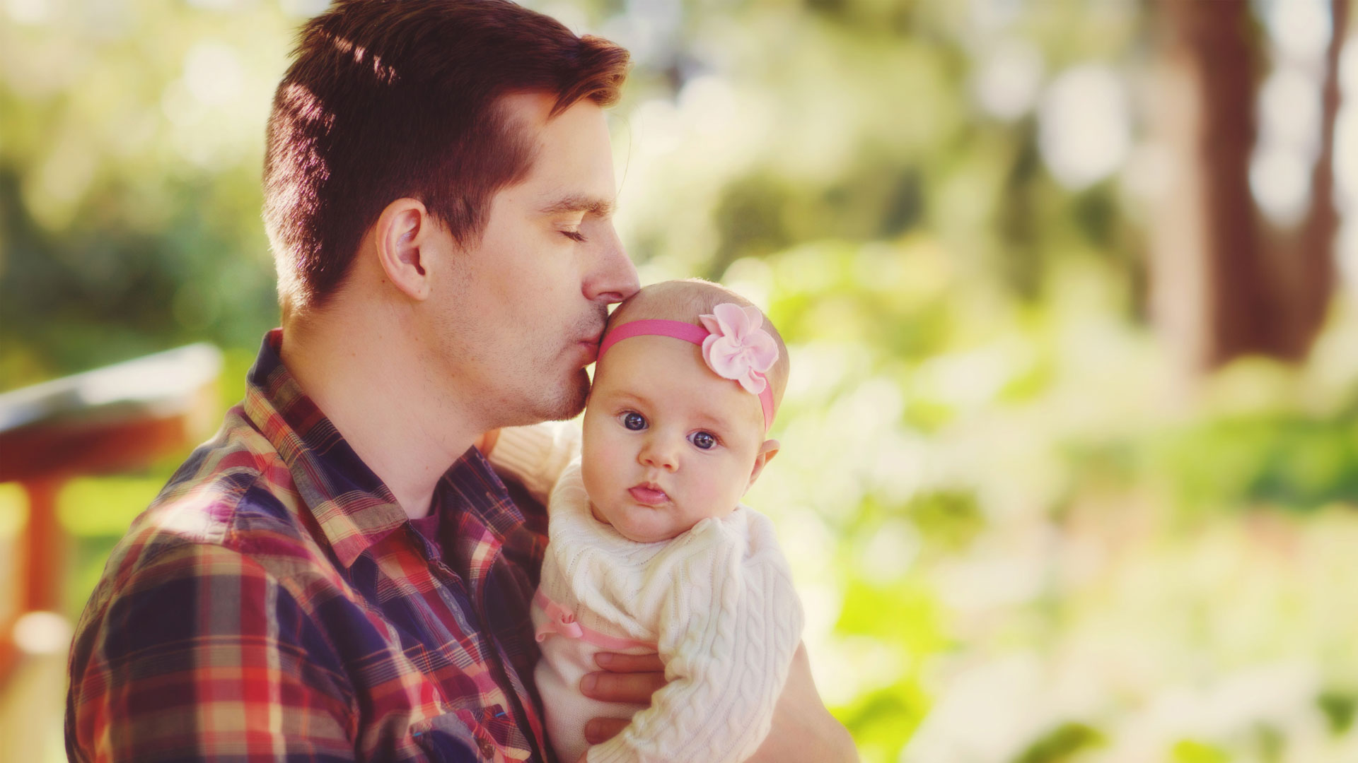 Father kissing infant daughter on Father's day