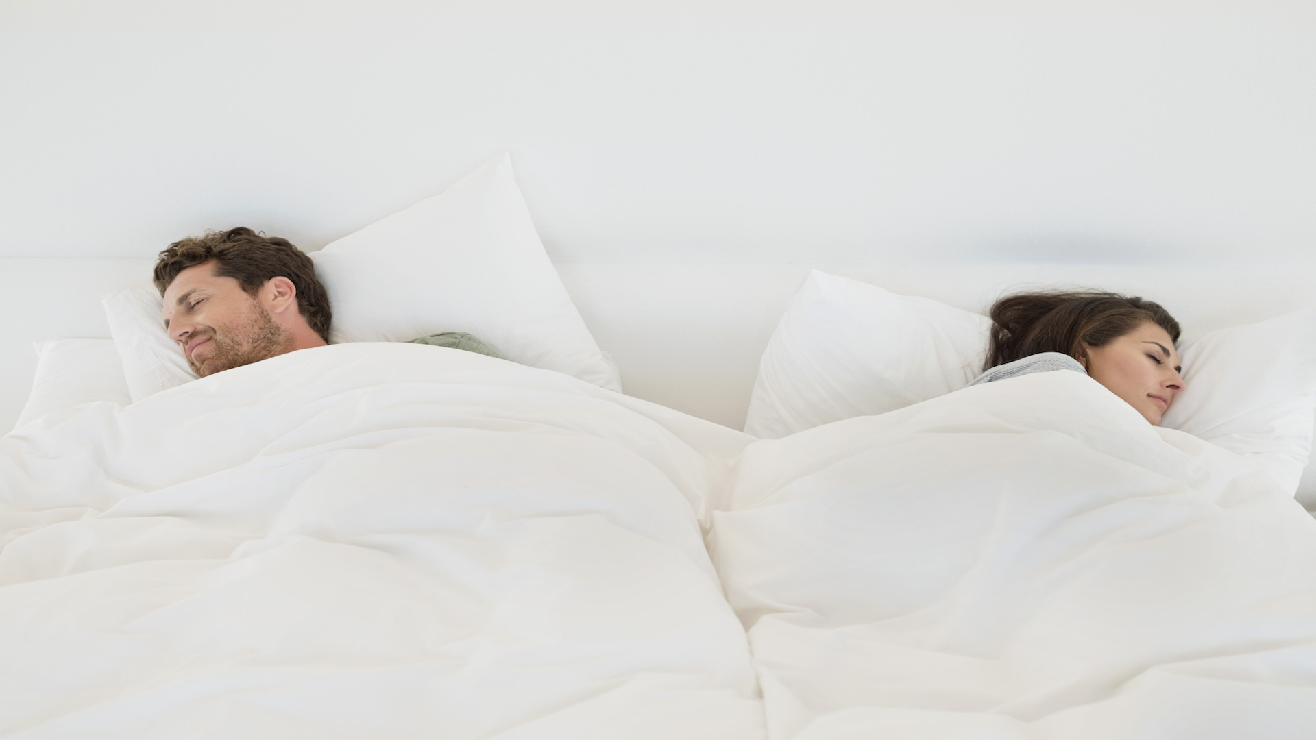 Man and woman sleeping on opposite sides of the bed