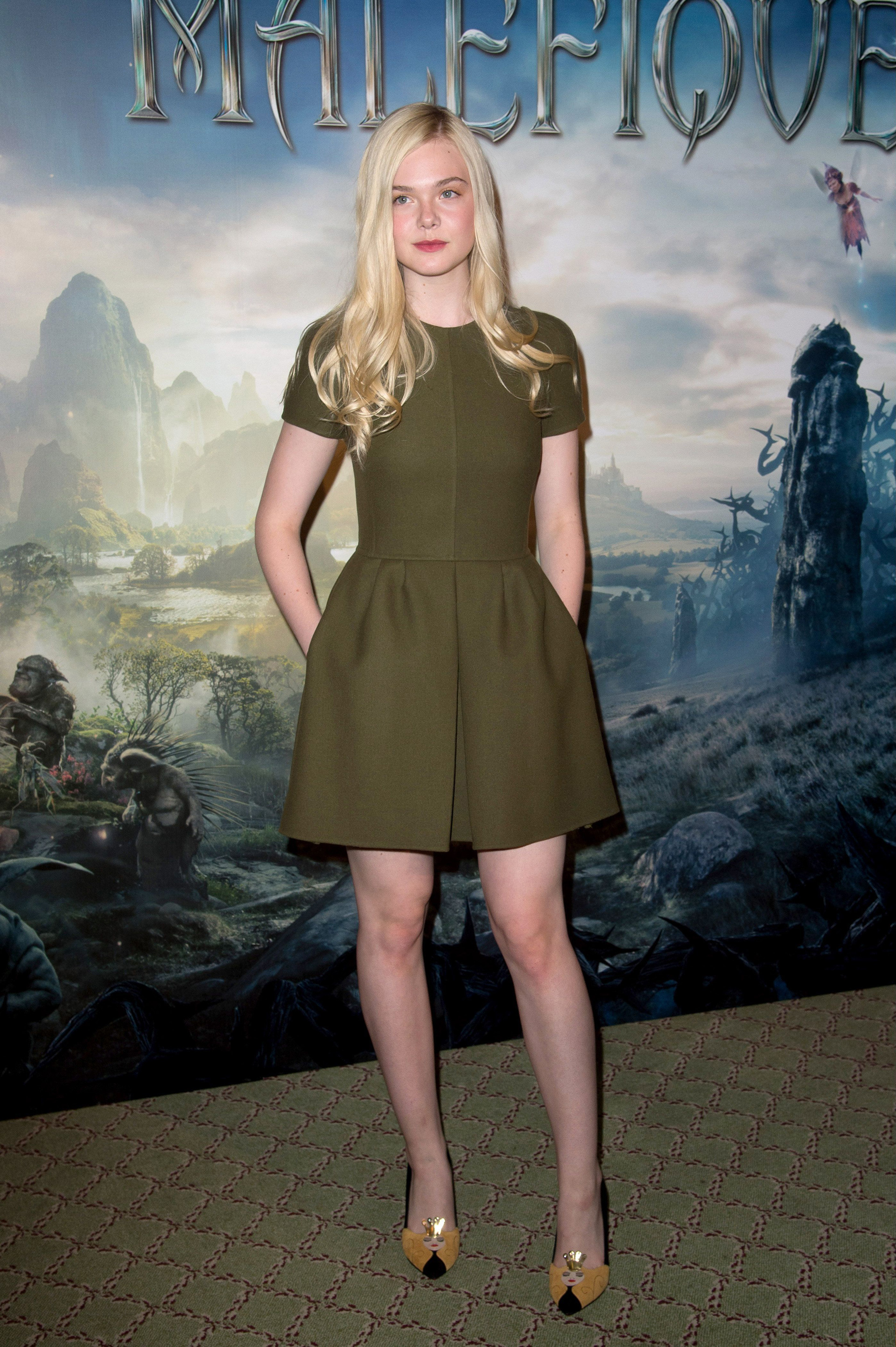 Elle Fanning at Maleficent photo call wearing a fit and flare army green dress