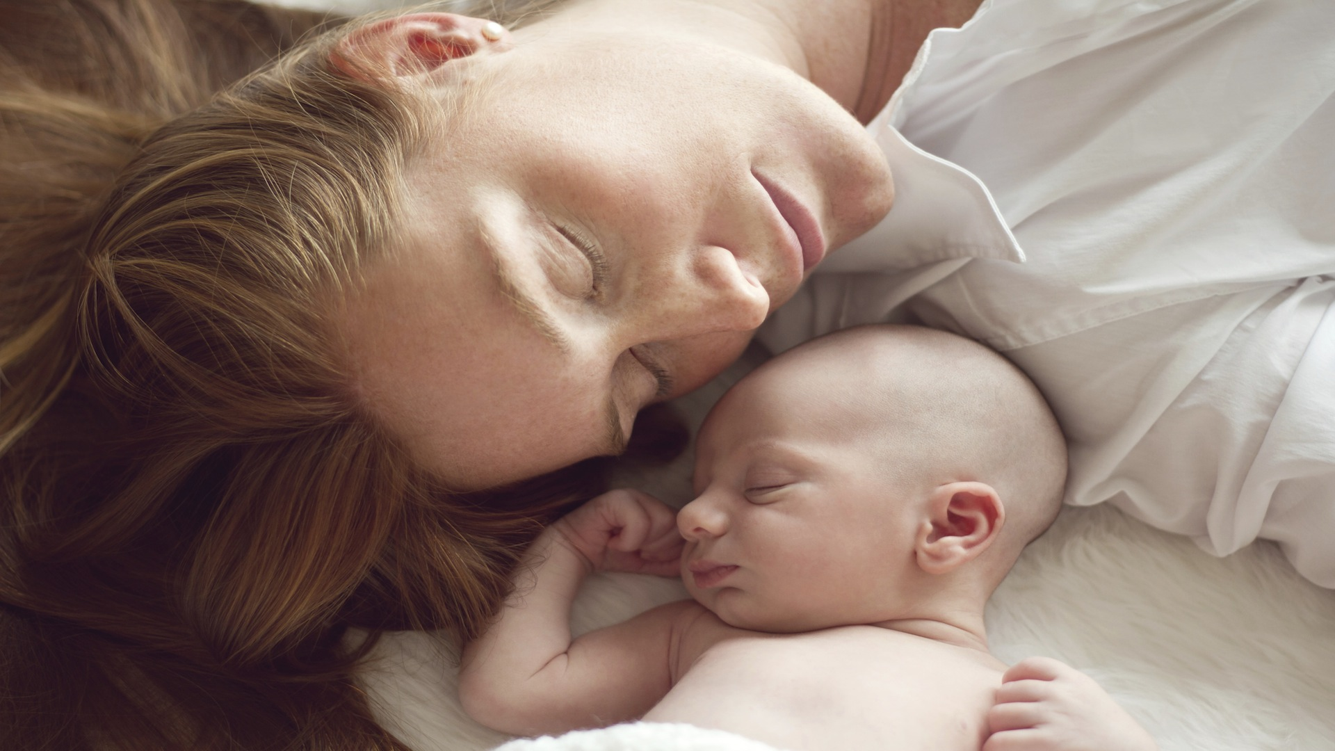 Mom resting head to head with her newborn