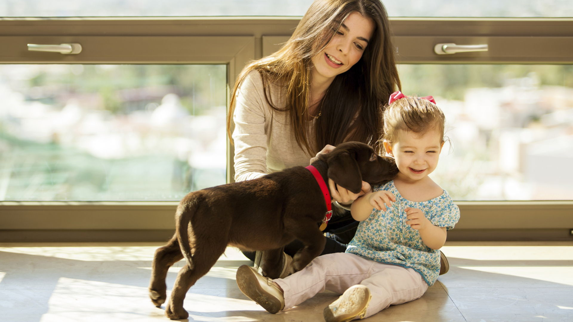 Mother and daughter playing with puppy | Sheknows.com