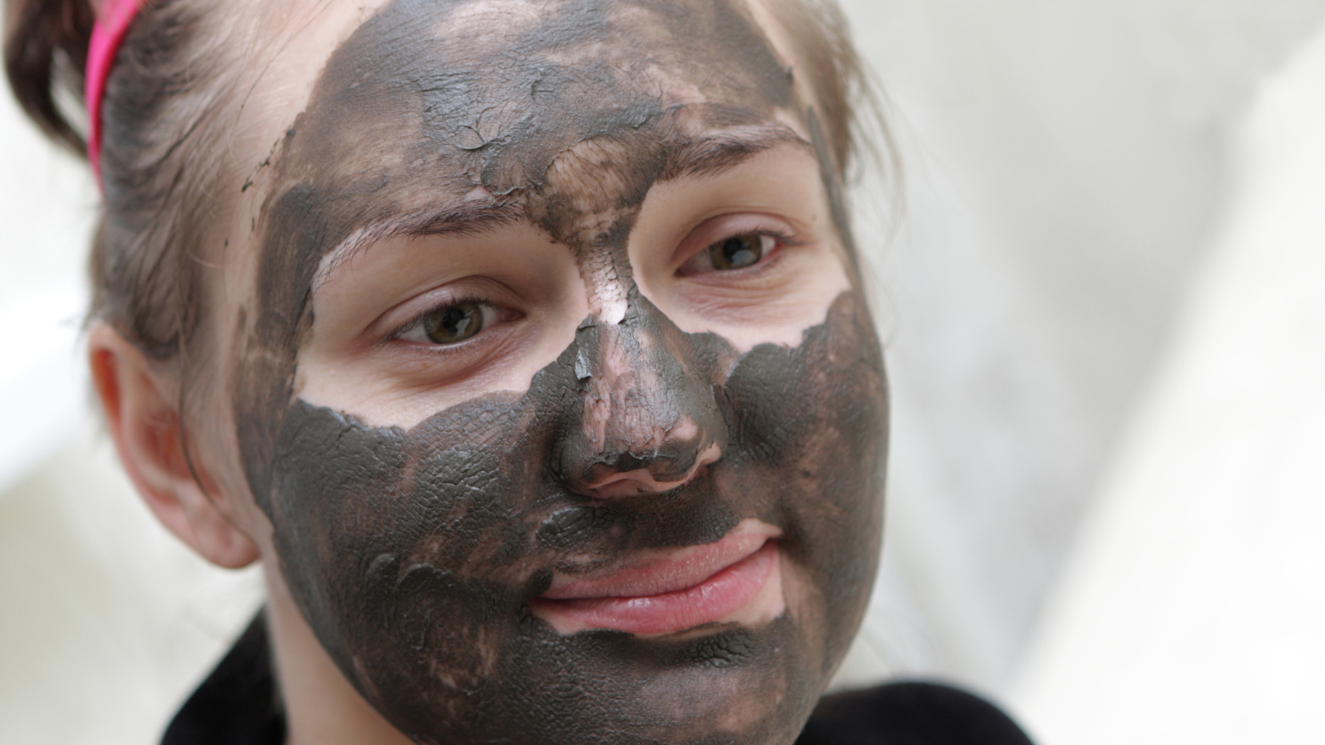 Woman washing face with charcoal cleanser