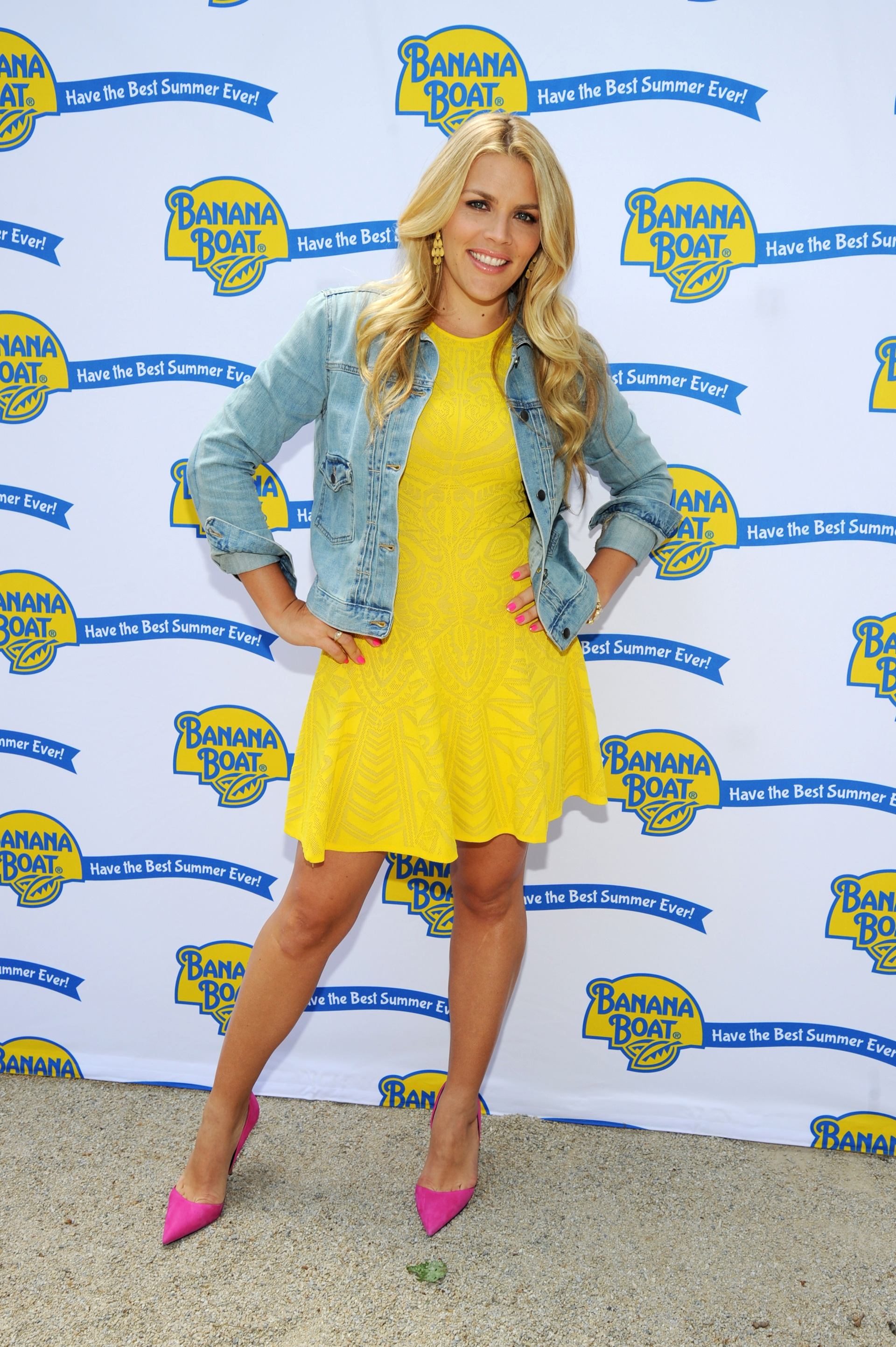 Busy Philipps wearing a bright yellow dress and jean jacket