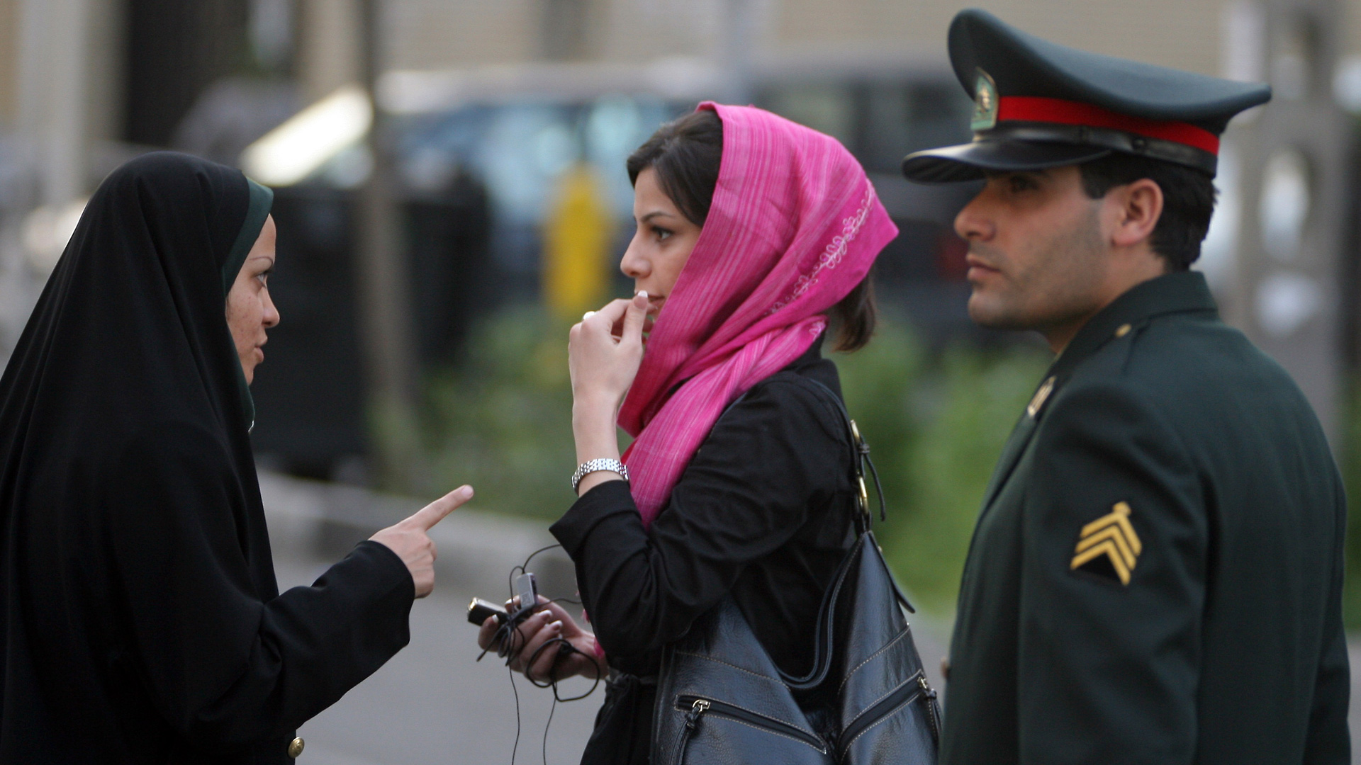 An Iranian policewoman (L) warns a woman about her clothing and hair during a crackdown to enforce Islamic dress code on April 22, 2007 in Tehran, Iran. (Photo credit: Majid Saeedi/Getty Images)