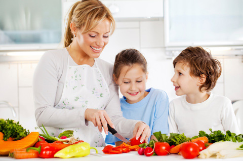 Mother and children cutting vegetables