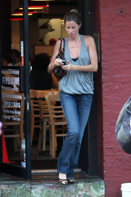 Giselle Bundchen checking her phone in Soho