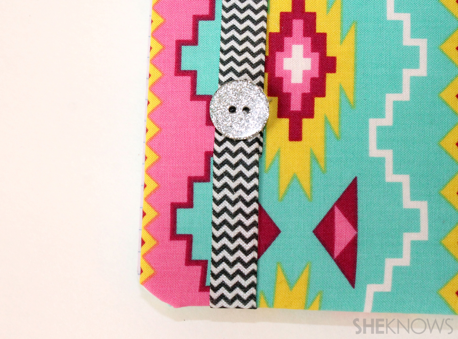 fabric covered composition book: Loop the decorative elastic around the book