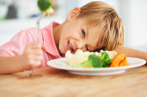 A picky eater with a plate of vegetables