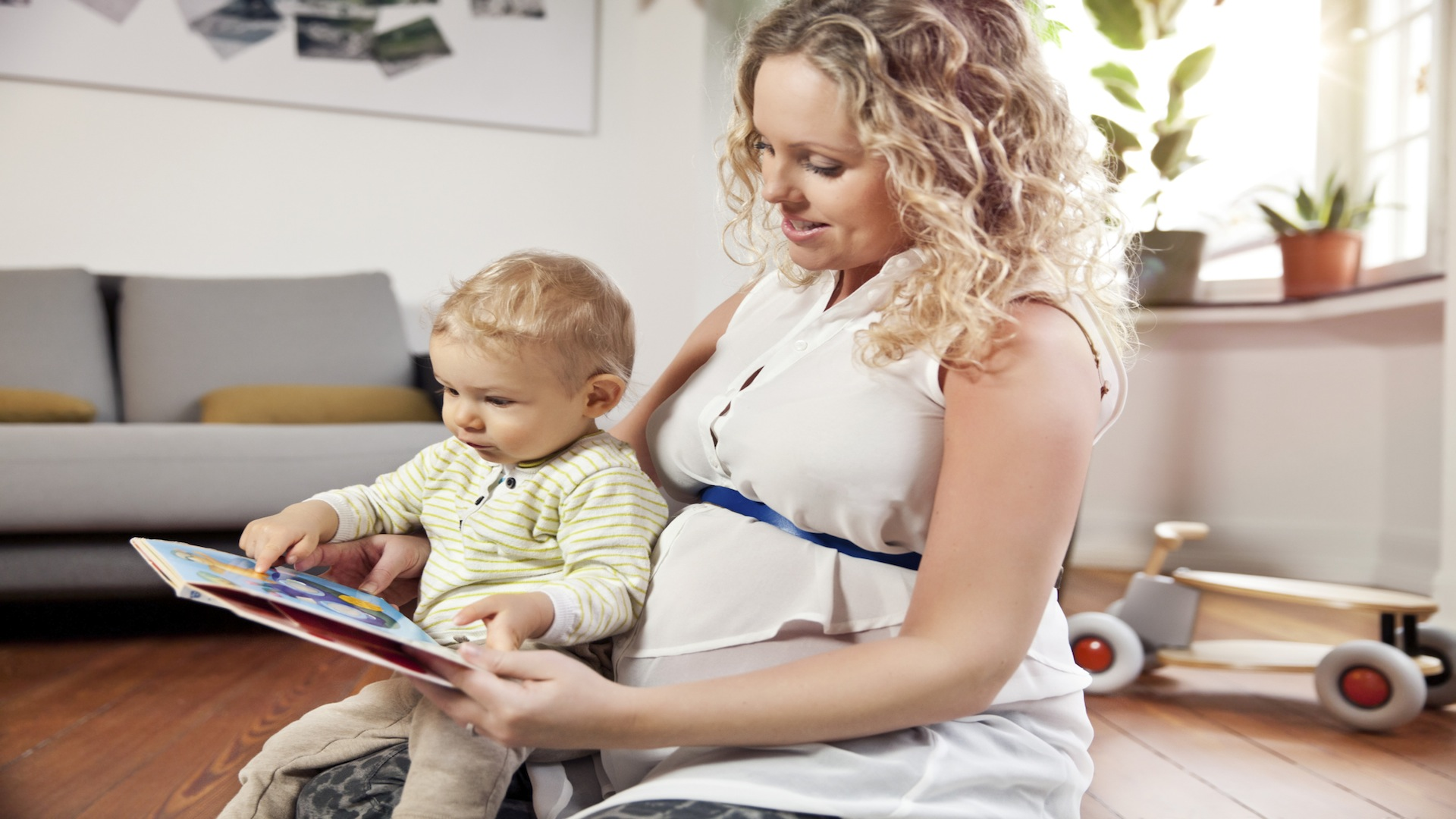 Pregnant woman reading baby book