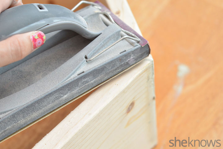 Use a piece of sandpaper to sand down the wood filler until the ...