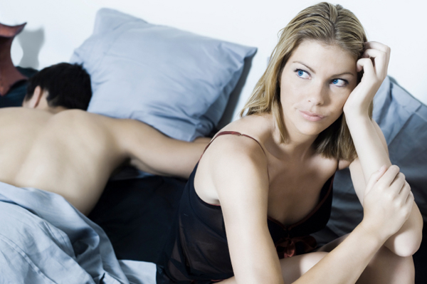 Bored woman in bed with spouse
