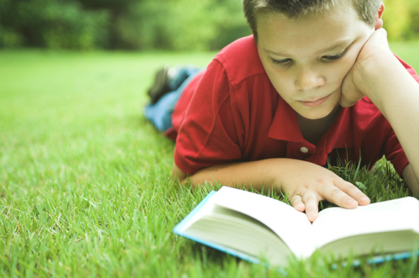 Boy reading book outside