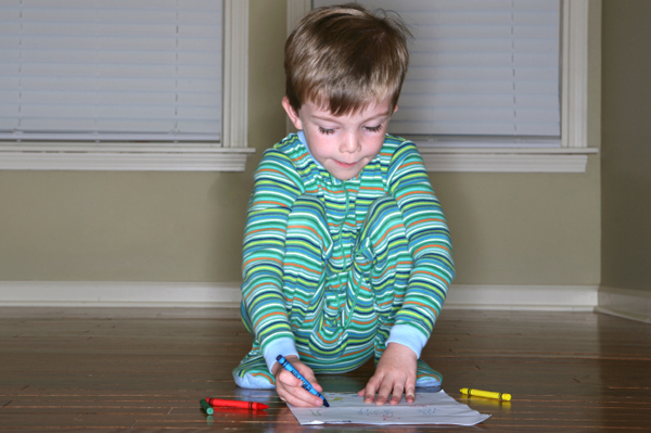 Child coloring in pajamas