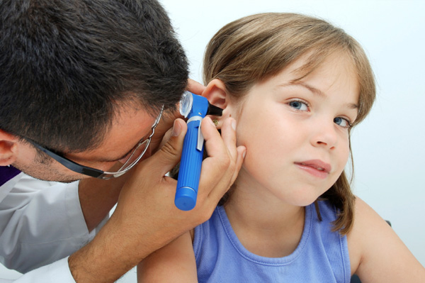 Child with ear infection at doctor