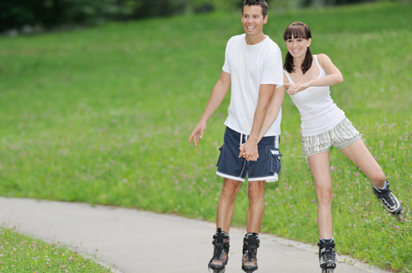 Couple roller skating in park