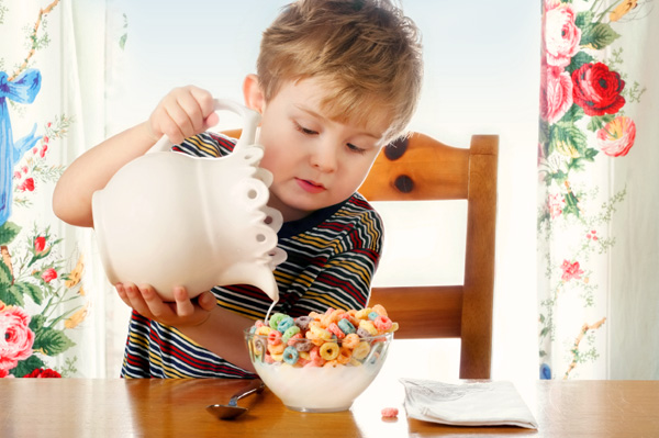Child pouring milk into cereal on his own