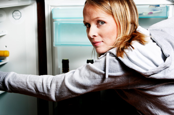 College Girl Looking in to Refrigerator