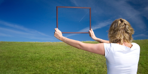 Woman with frame on big meadow