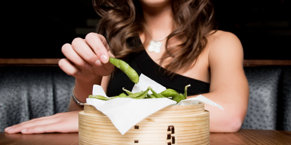 Woman eating Edamame Beans.