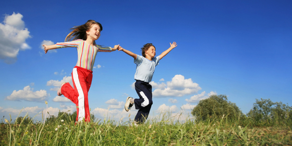 Girl and Boy Running in Meadow