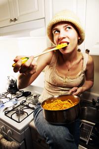 Woman eating macaroni and cheese.