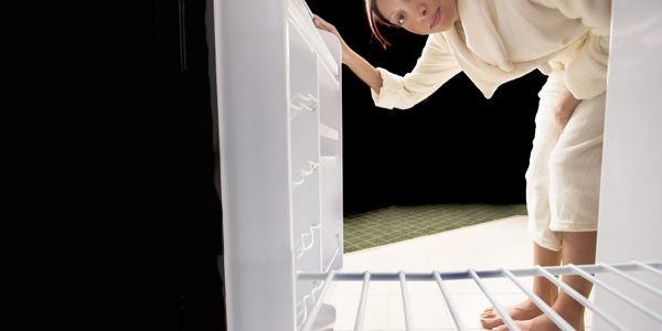 Woman looking into an empty refrigerator