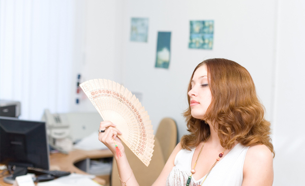 Woman holding fan in office.