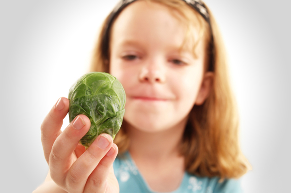 Girl looking at brussels sprout