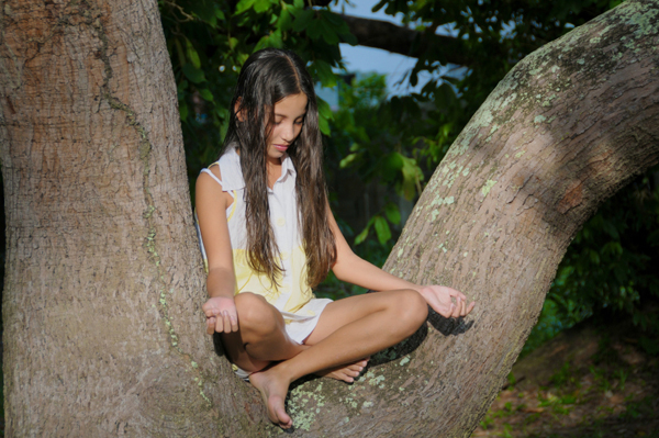 Girl meditating in tree