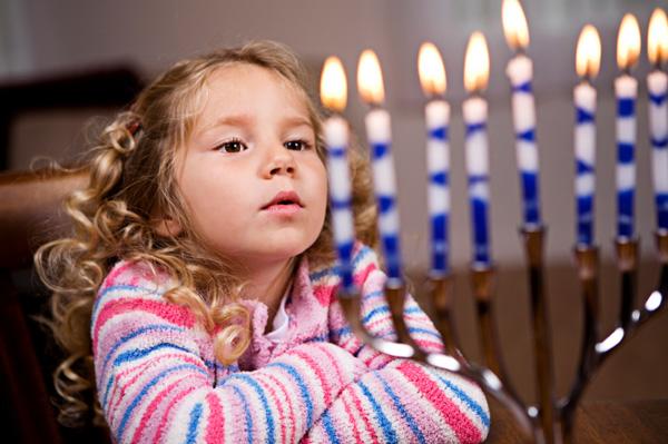 hanukkah child looking at mennorah