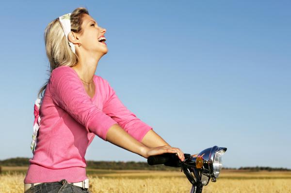 Happy woman riding bike near field