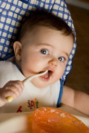 baby in high chair eating puree