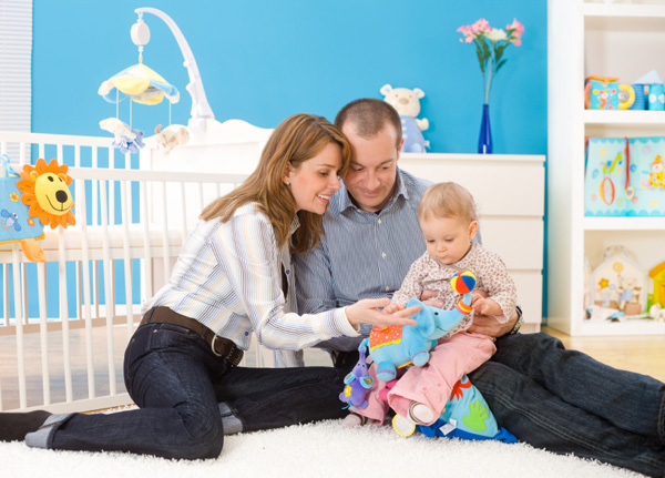 parents and baby in nursery room
