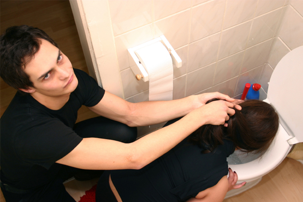 Man holding woman's hair back as she vomits