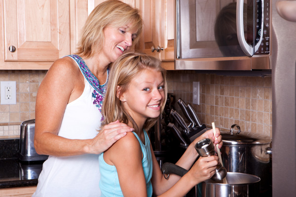 Mom with tween girl cooking
