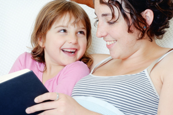 Mom reading book with daughter
