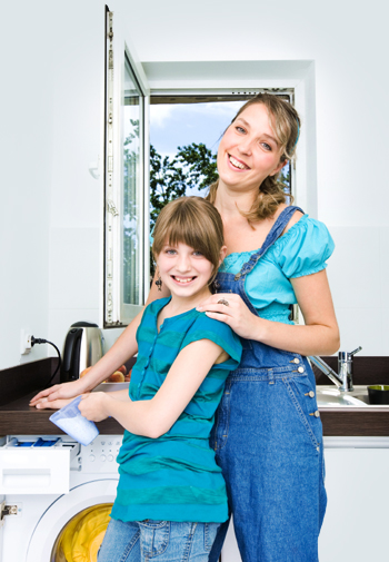 Mother teaching daughter how to do laundry